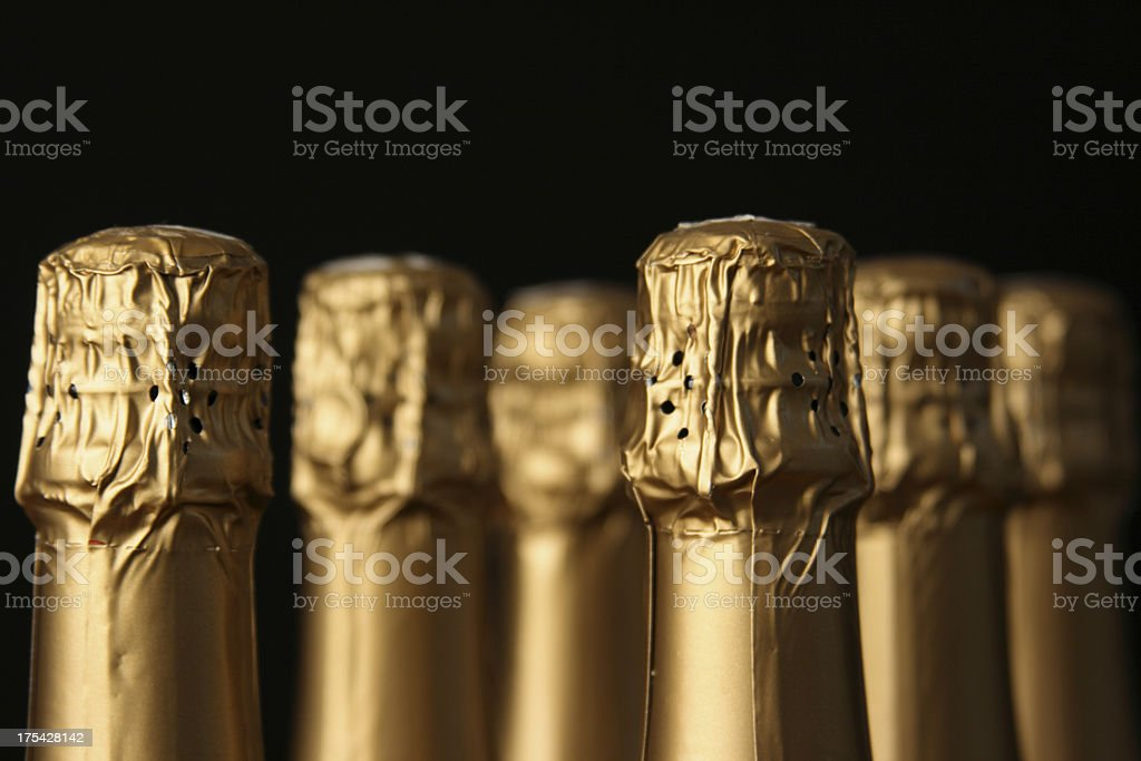 Festive Gold Foil Champagne Bottles for Celebration in Black Background royalty-free stock photo
