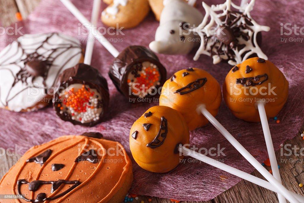 Festive Halloween cake pop and gingerbread close-up. horizontal stock photo