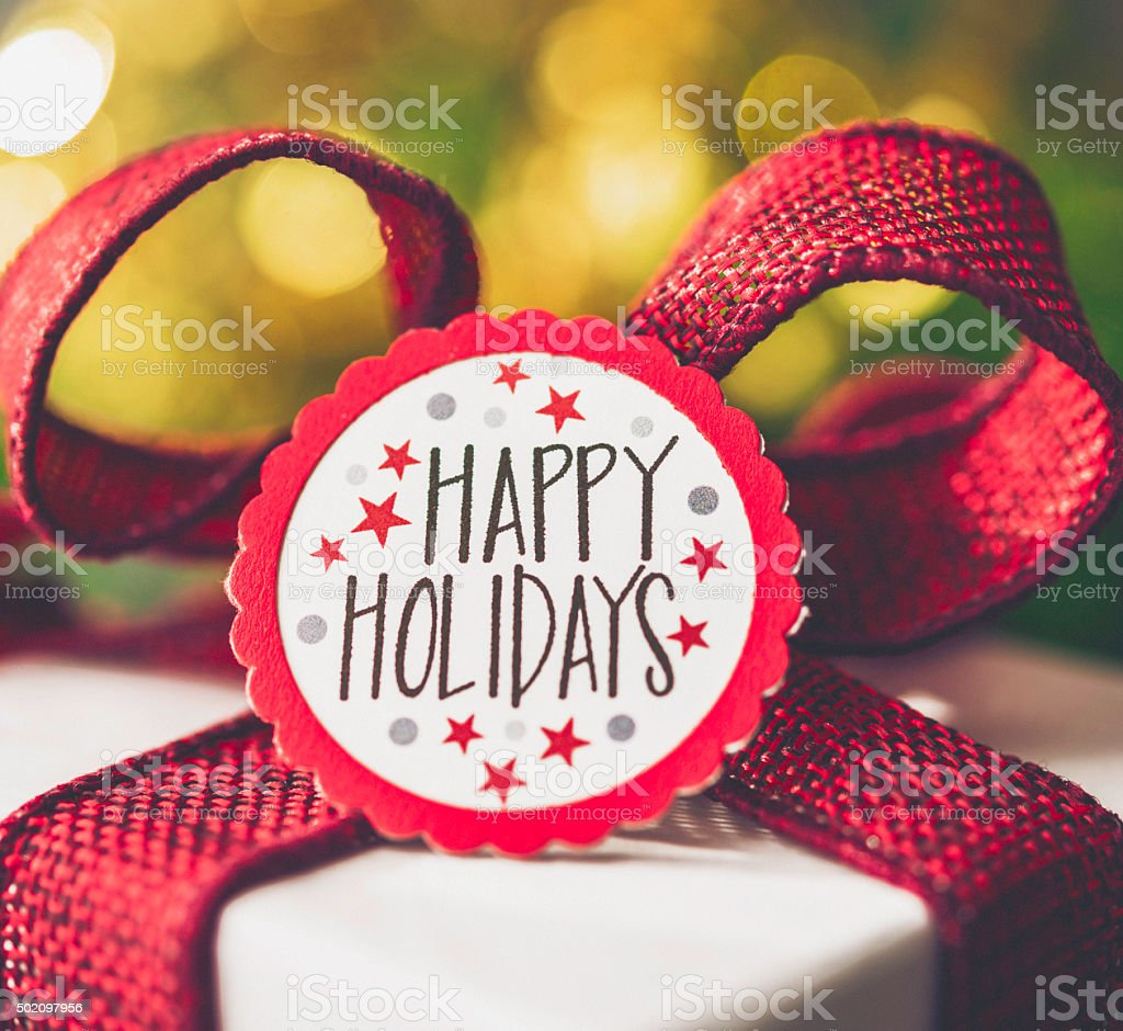 Festive holiday gift with red ribbon against red bokeh background stock photo