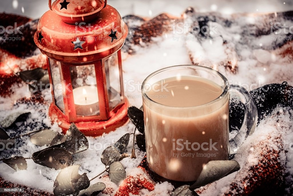 Festive red candle in lantern and mug of coffee on stock photo