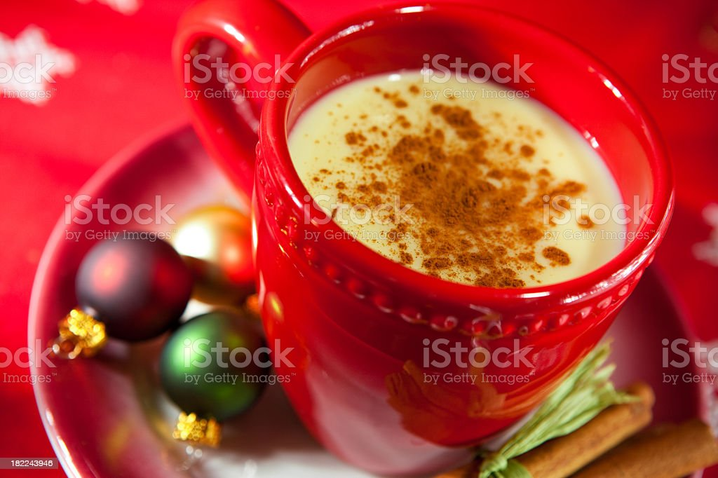 Festive red cup & saucer of egg nog with Christmas baubles  royalty-free stock photo