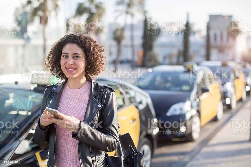 Fetching a taxi with smart phone app. stock photo
