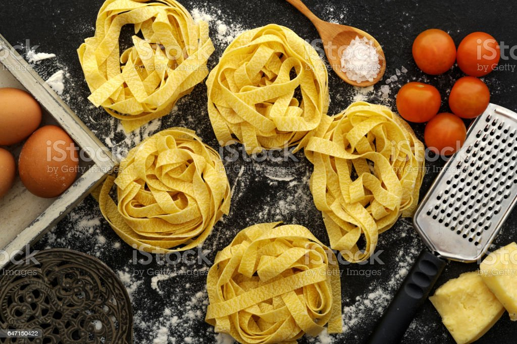 Fettuccine pasta italian food still life rustic over black wood background. stock photo
