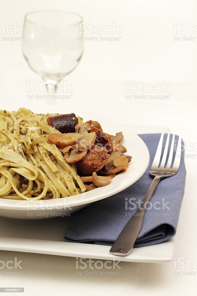 Fettuccine with pesto and sausage stock photo