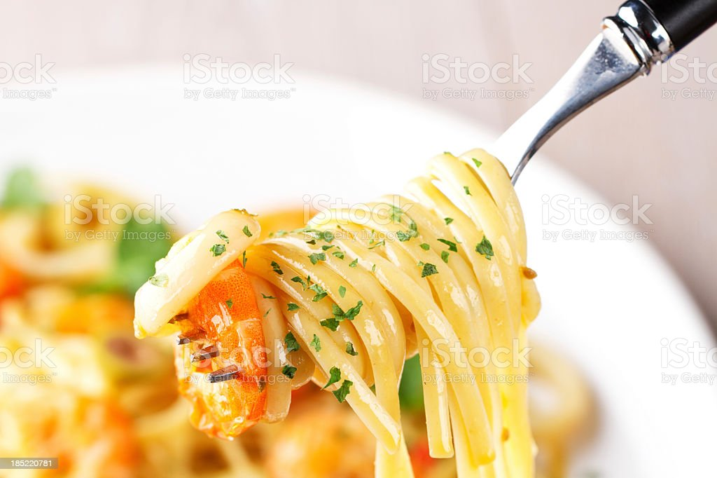 Fettuccine with shrimp and squid on a fork stock photo
