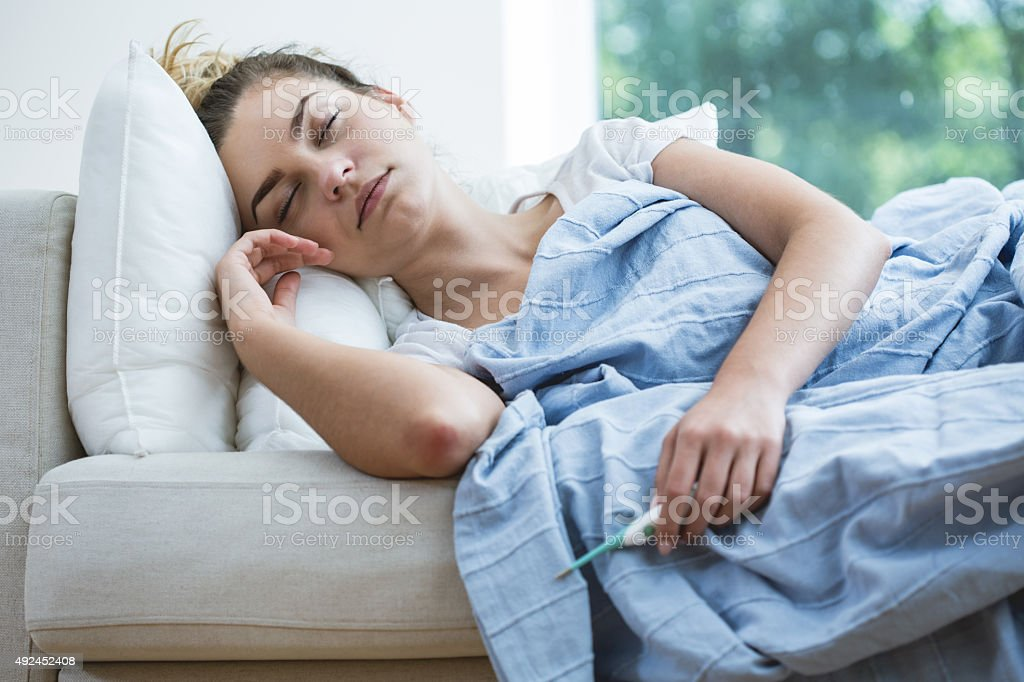 Feverish woman lying under blanket stock photo