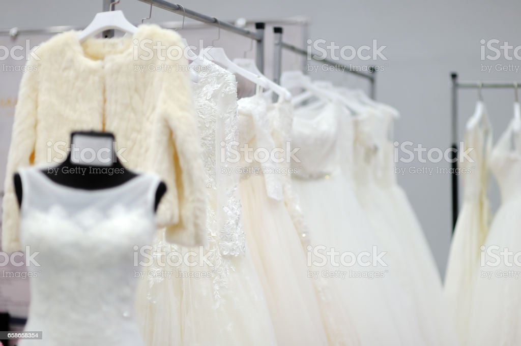 A few beautiful wedding dresses and fur coat on a hanger stock photo