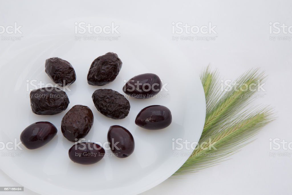 few dark black olives on a white plate and three green spikes on a white mesh background with an empty place for the inscription stock photo