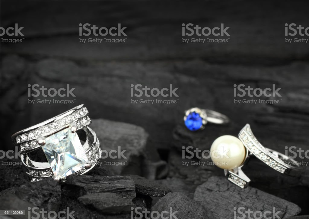 Few jewelry rings with brilliants, gems and pearl on black coal background, soft focus stock photo
