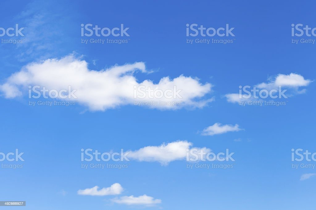 few little fluffy white clouds in blue sky stock photo