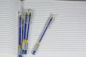 Few Pens On A Copybook Sheets.