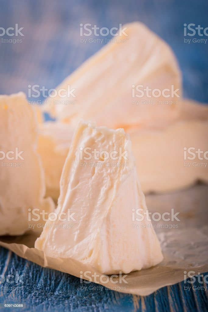 Few portions of camembert cheese on blue board stock photo
