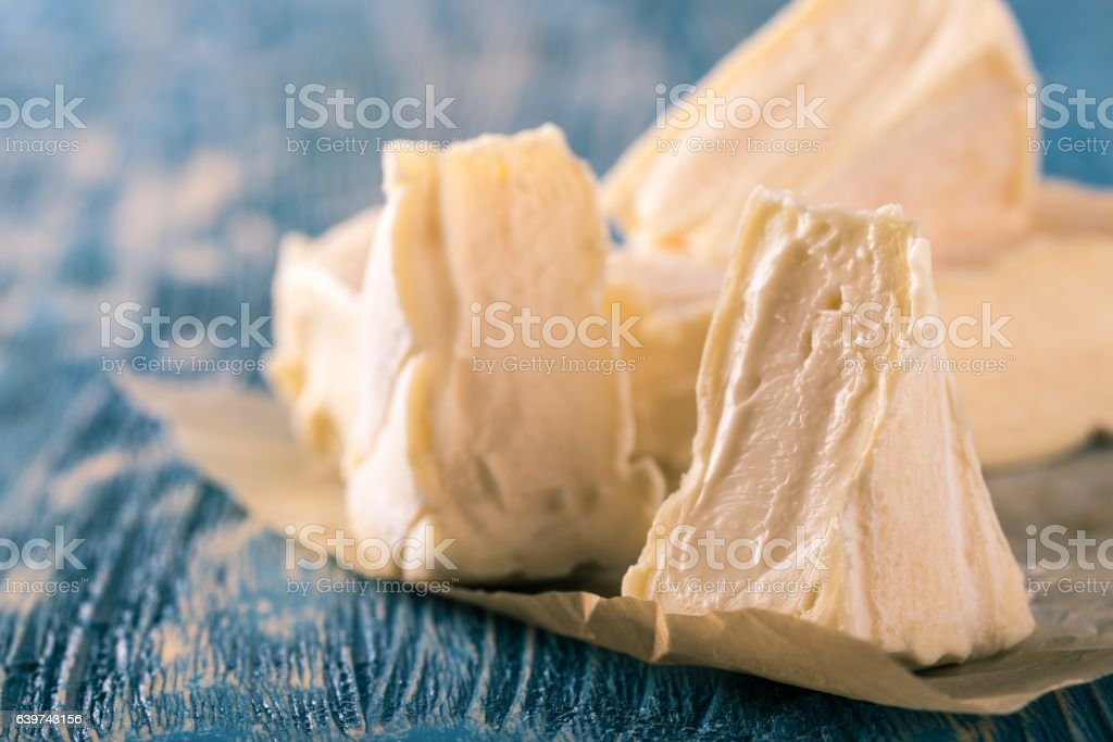 Few portions of camembert cheese on blue wooden board stock photo