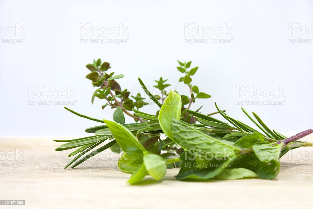 A few sprigs of fresh herbs on a table royalty-free stock photo