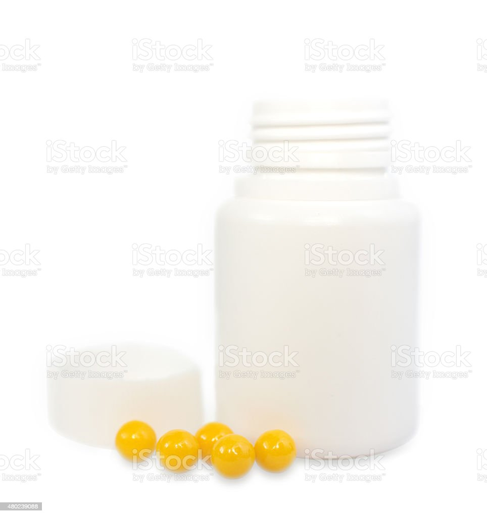 few yellow coated tablets on a white plastic jars stock photo