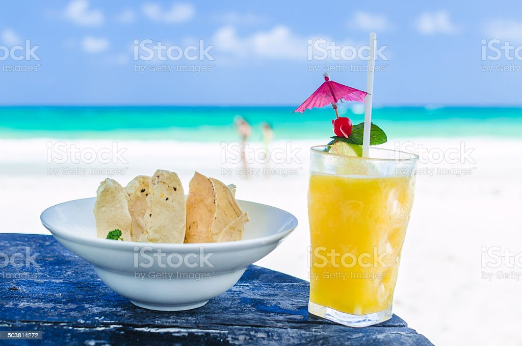 FFresh alcohol cocktail and nachos at tropical exotic Caribbean beach stock photo
