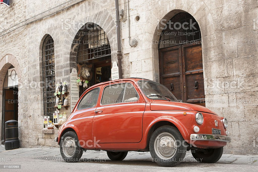 Fiat 500 car against traditional Italian architecture. stock photo