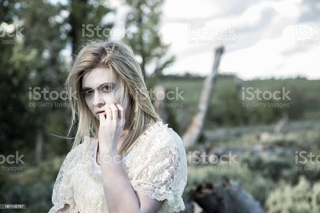 Fictional Character:  Haunting, sad ghost woman in forest. White dress. royalty-free stock photo