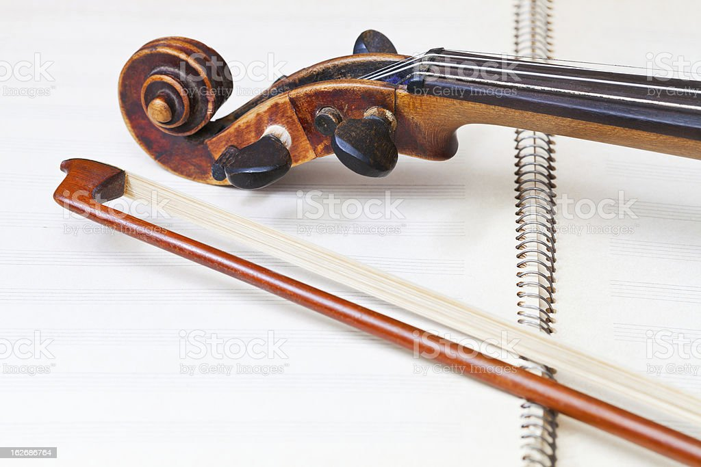 fiddle bow and scroll on music book royalty-free stock photo