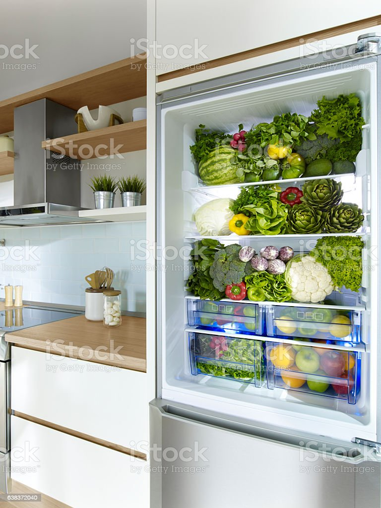 Fidge filled up with green vegetables and fruit stock photo