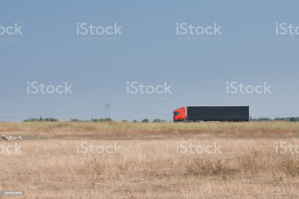 field and a truck passing on the highway royalty-free stock photo