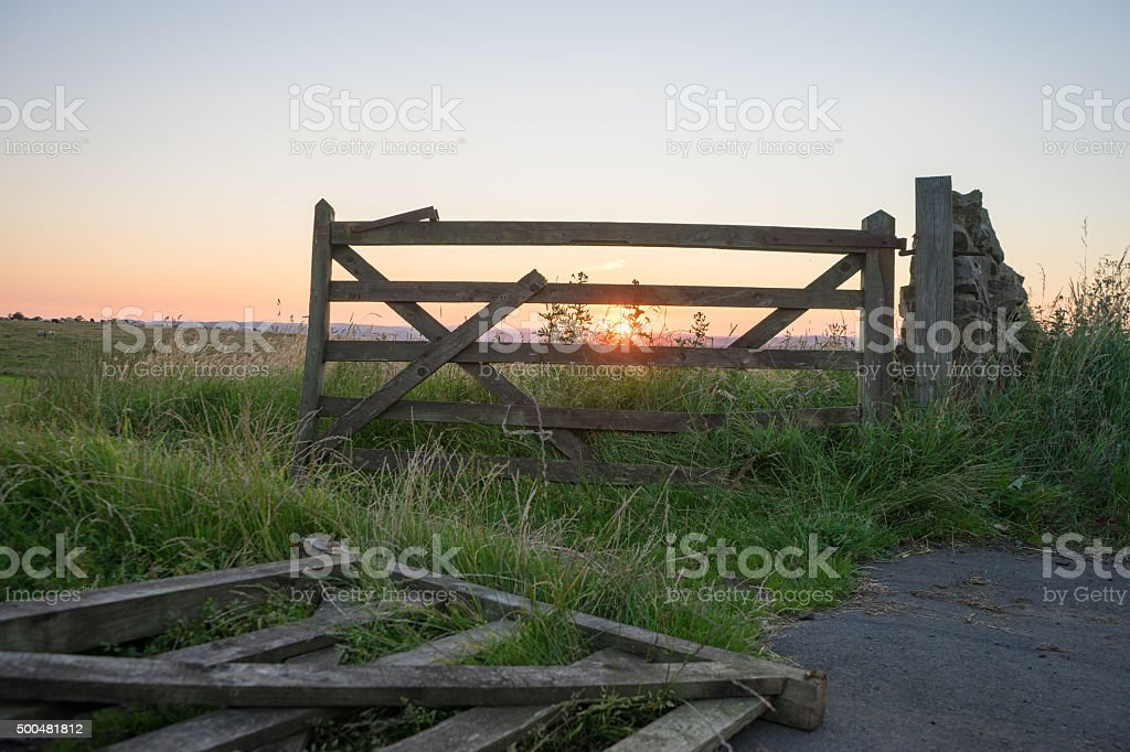 Field fence post with sunset stock photo