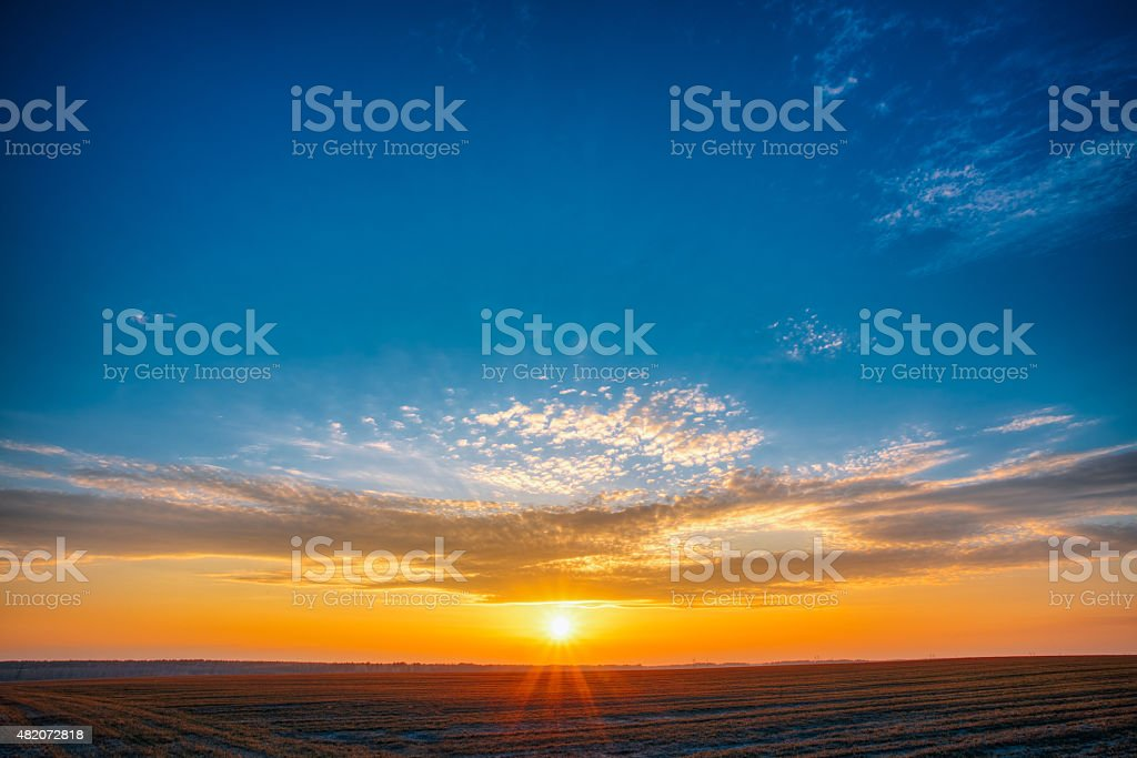 Field Meadow Road Under Sunset Sunbeams At Dawn Or Sunrise stock photo
