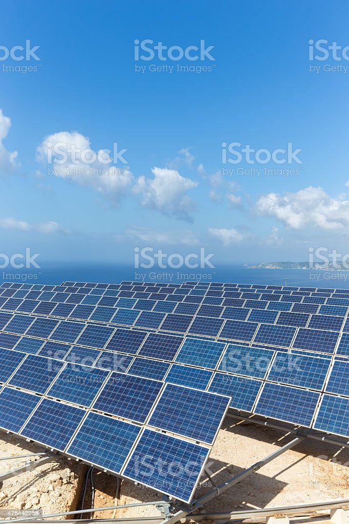 Field of solar collectors near sea with blue sky stock photo
