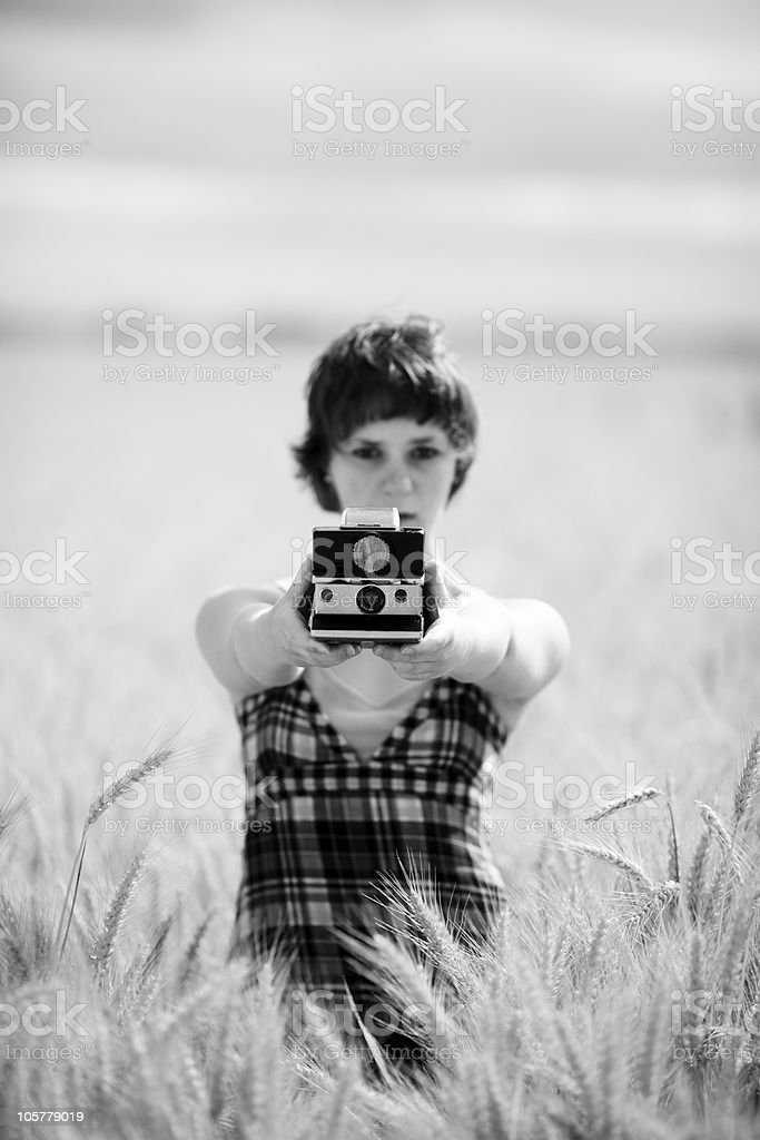 Field standing woman holding an instant camera stock photo