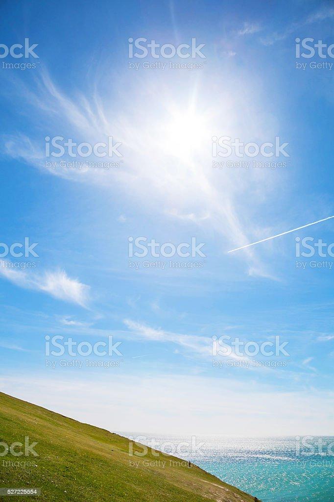 Field, sunrise, sea and blue sky stock photo