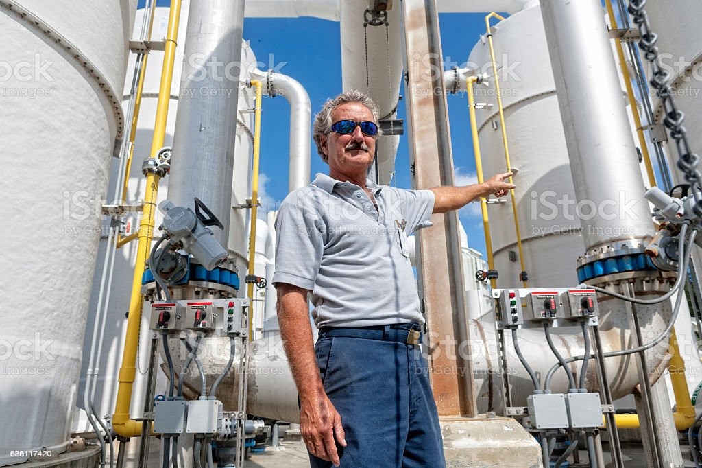 Field Technician Pointing to Chemical Tank stock photo