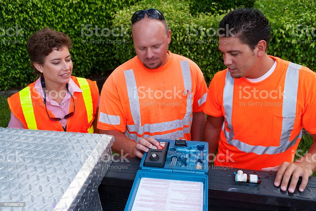 Field Technicians and Supervisor Testing Water stock photo