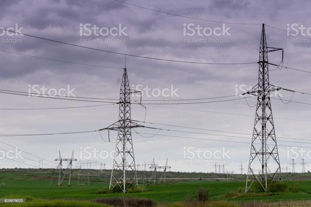 Field with poles for high voltage against a cloudy sky. stock photo