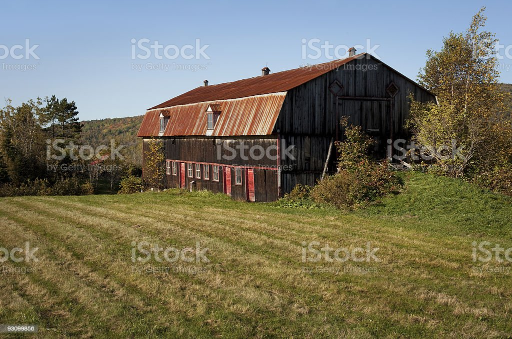 Field with red roofed barn stock photo