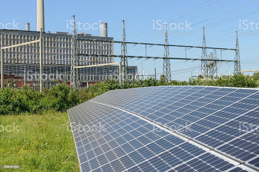 Field with solar cells in front of a power plant stock photo