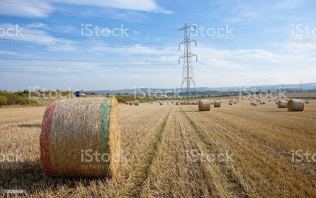 Field with wheat straw bales and pylon royalty-free stock photo