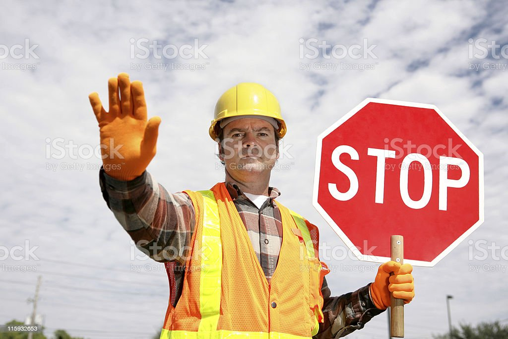 A field worker holding a STOP sign and raising one hand stock photo