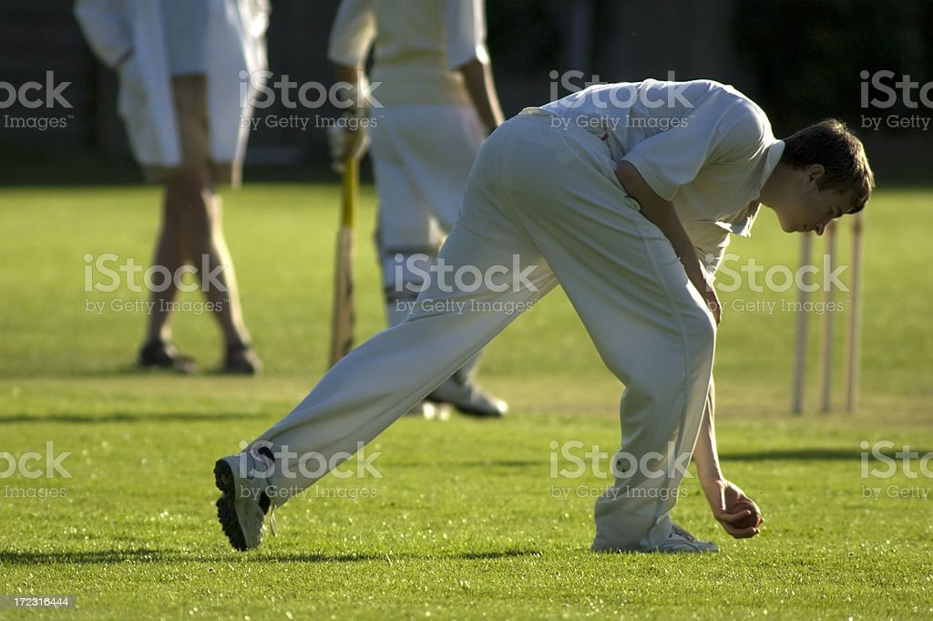 Fielder picking up ball during cricket game royalty-free stock photo