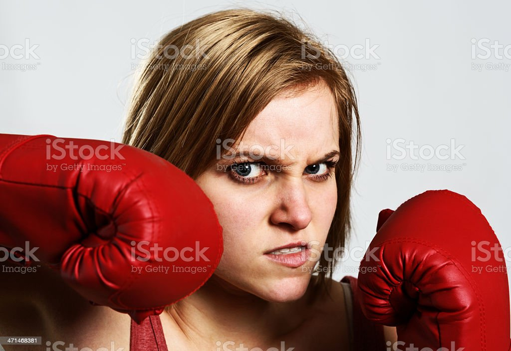 Head and shoulders portrait of an angry young blonde female boxer,...