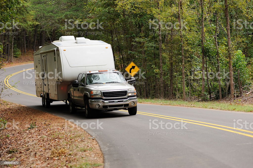 Fifth wheel being pulled down winding road stock photo