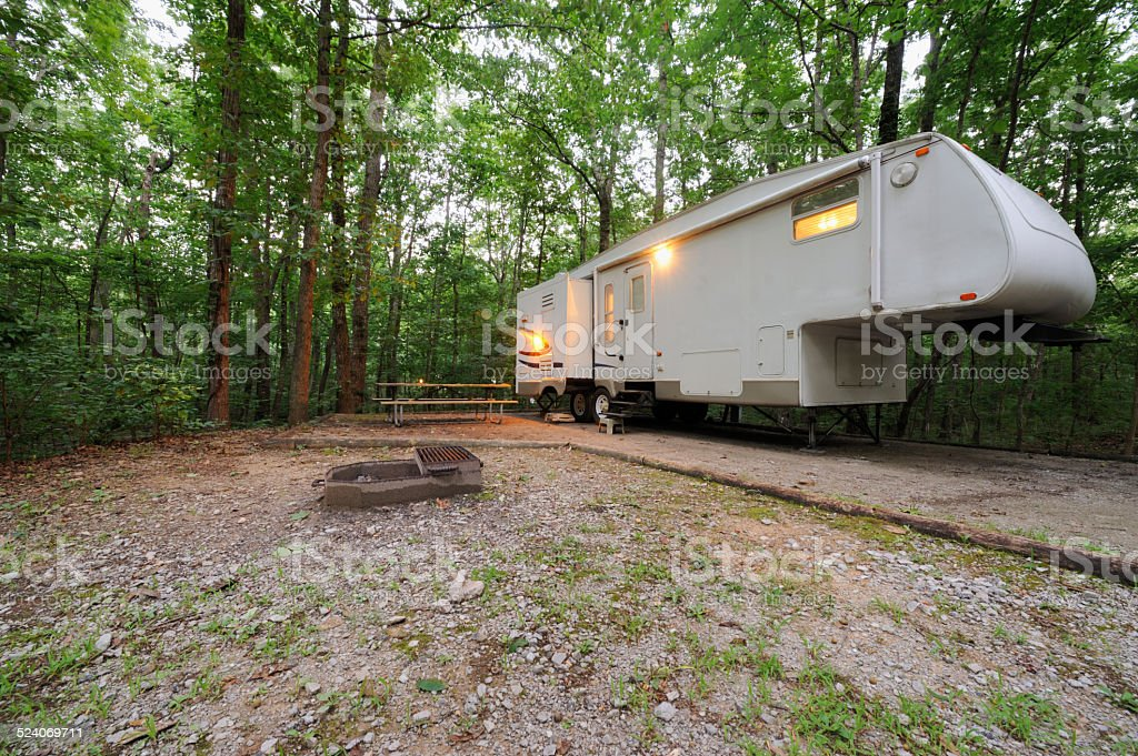 Fifth wheel travel trailer rv in campsite at dusk stock photo