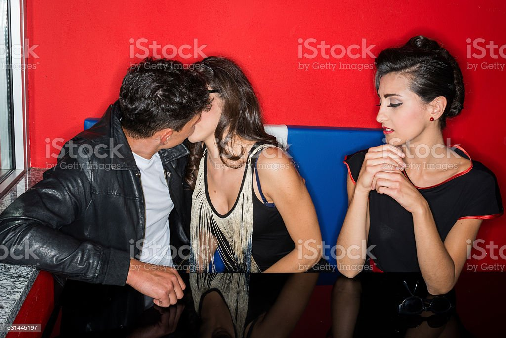 Fifties 1950s style ring flash portraits: couple kissing with friend stock photo