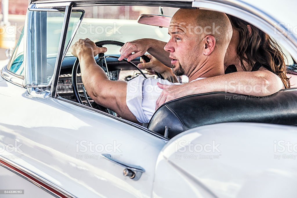Fifties Couple Driving Classic 1957 Car stock photo