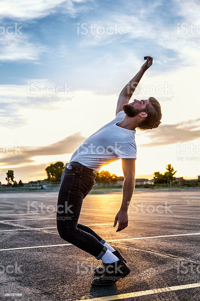 Fifties Greaser Bending Backwards in Sunset stock photo