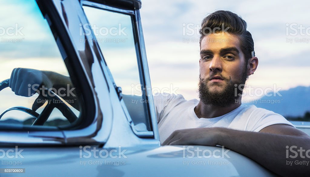Fifties Pompadour Greaser Hipster Guy Driving Classic Convertible Car stock photo