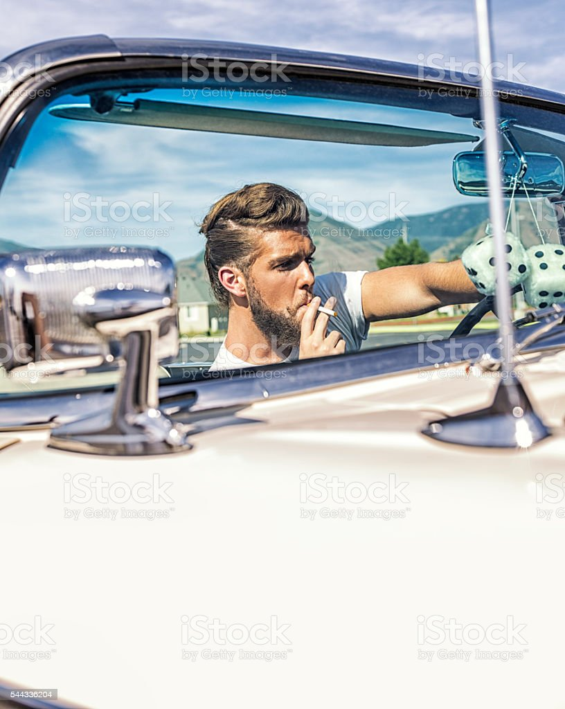Fifties Pompadour Hair Greaser Guy Smoking Driving Convertible Car stock photo