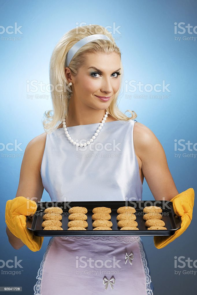 Fifties style housewife holding a full hot cookie tray stock photo