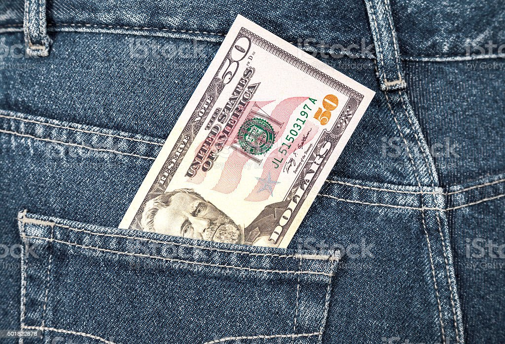 Fifty dollars bill sticking out of the back jeans pocket stock photo