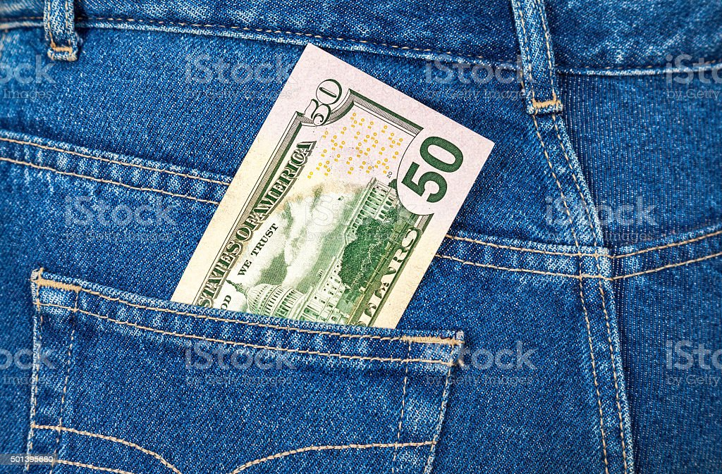 Fifty dollars bill sticking out of the blue jeans pocket stock photo
