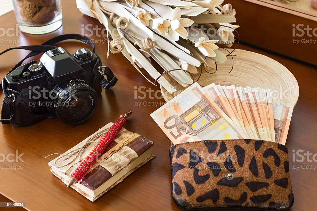 Fifty euro banknotes, camera, notebook and bouquet on table stock photo